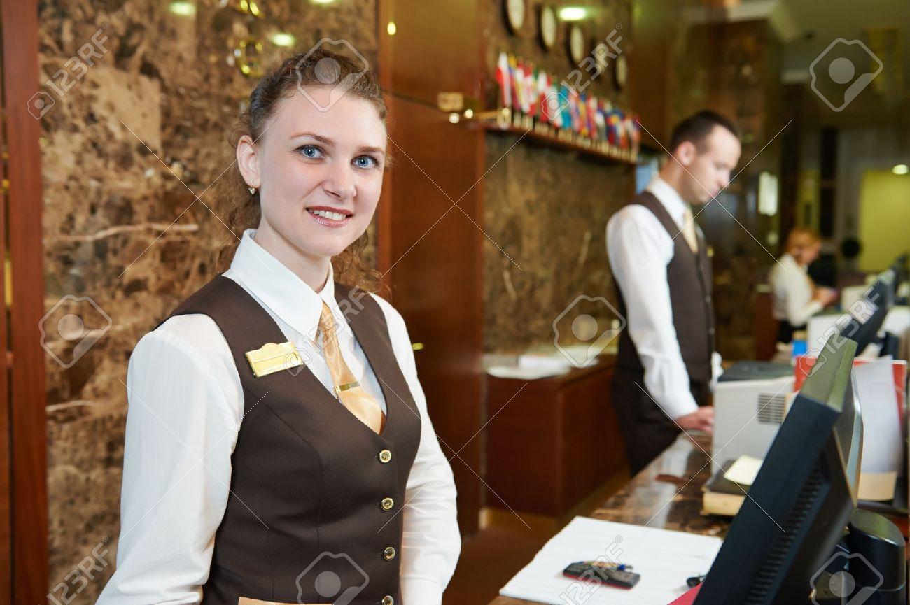 27855345-happy-female-receptionist-worker-standing-at-hotel-counter-stock-photo